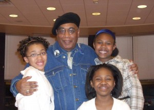 Photo of Larry Pinkney with 3 young audience members